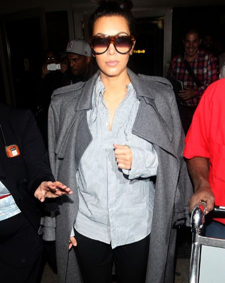 Kim Kardashian covered up her baby bump in baggy clothes as she went through Los Angeles airport