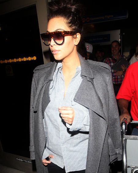 Kim Kardashian hid her trademark curves in a baggy pinstripe shirt and huge cosy looking coat